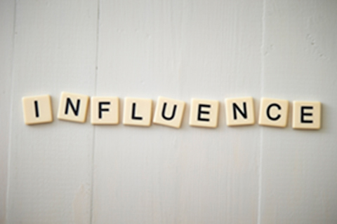 Scrabble letters spell the word Influence